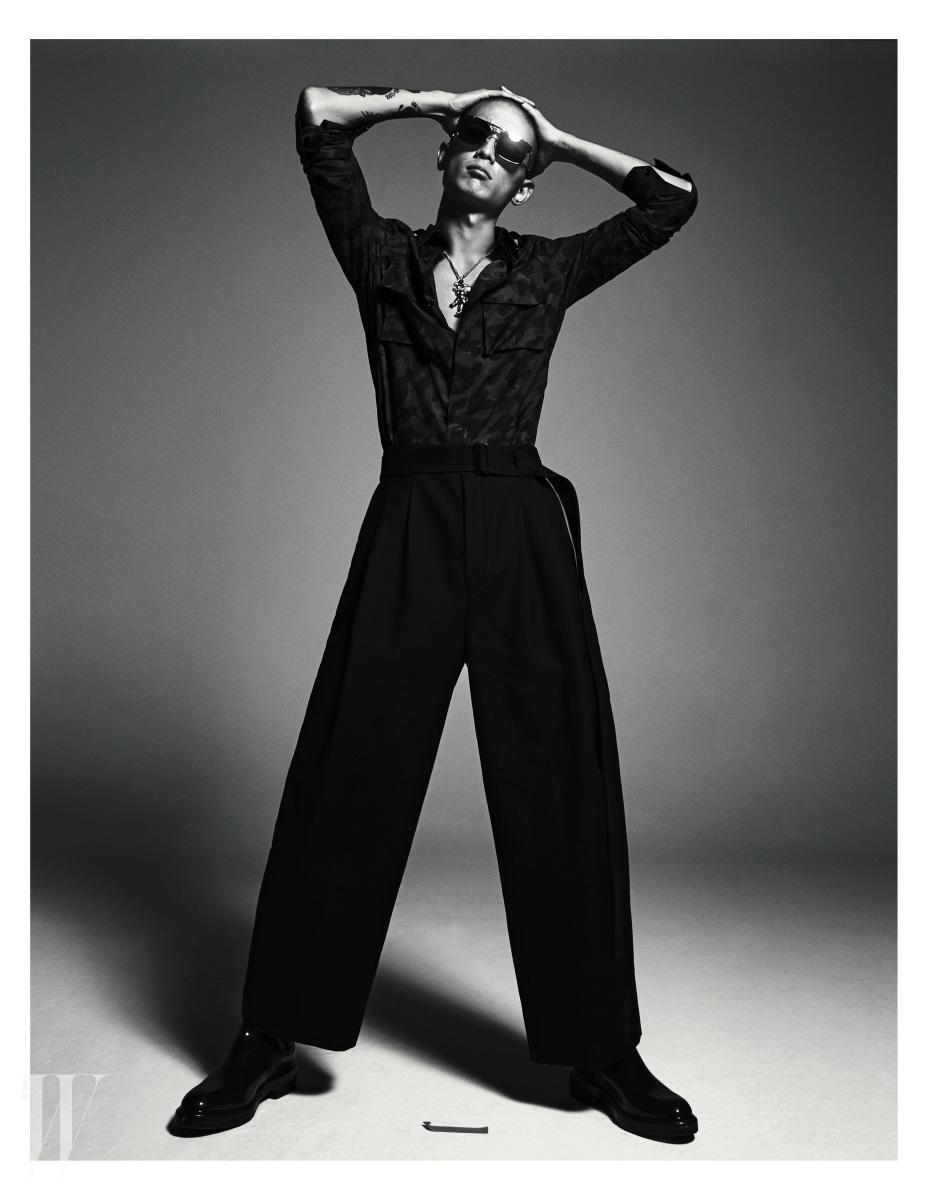 꽃무늬 셔츠와 검정 로퍼는 Louis Vuitton, 검정 팬츠는 Juun.J, 사자 장식 목걸이는 Jamie&Bell, 선글라스는 Linda Farrow by Safilo 제품.