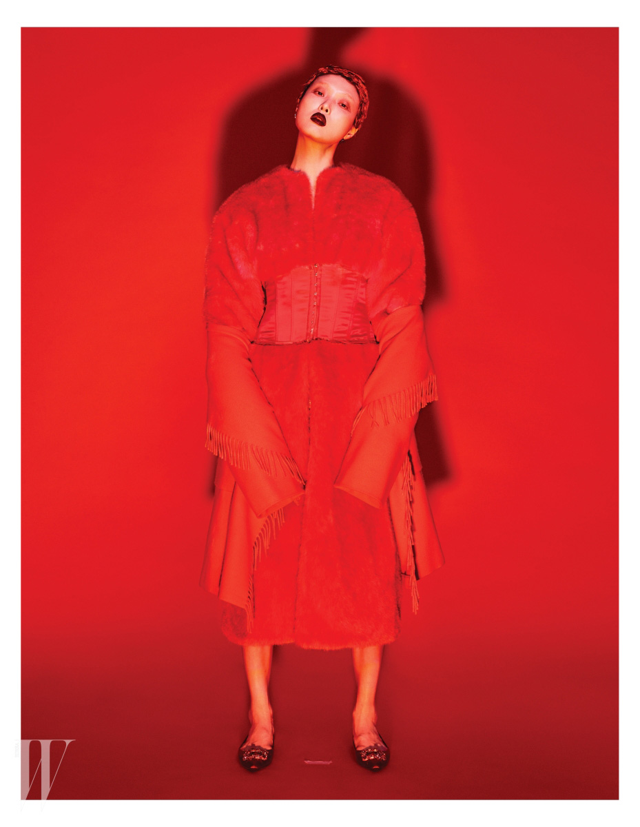 코르셋 장식이 허리에 들어간 빨강 퍼 코트는 Push Button, 겹쳐서 연출한 프린지 장식 후드 판초는 Escada, 빨강 플랫 슈즈는 Roger Vivier 제품.