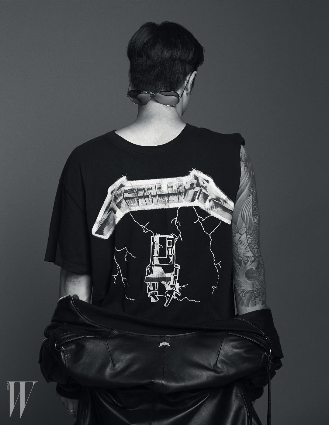 메탈리카 로고의 검은색 티셔츠는 Fear of God, 검은색 가죽 보머 재킷은 Nudebones, 보잉 선글라스는 Linda Farrow by Handock 제품.