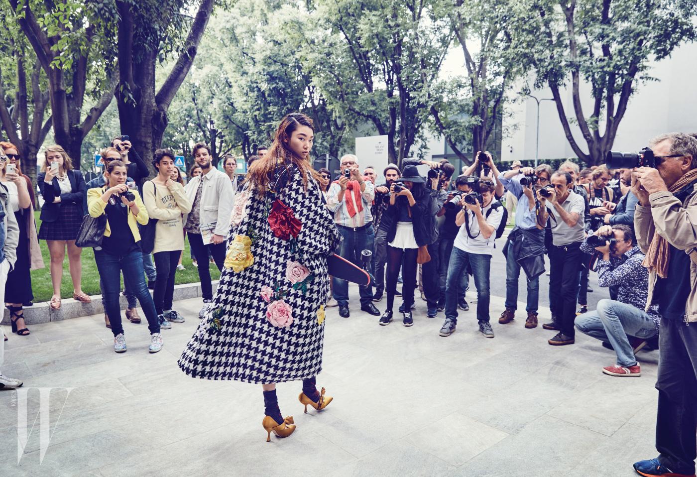 입체적인 꽃 장식의 하운즈투스 체크무늬 코트는 Dolce & Gabbana, 후디 재킷과 양말은 Prada, 리본 장식 힐은 Moschino 제품.