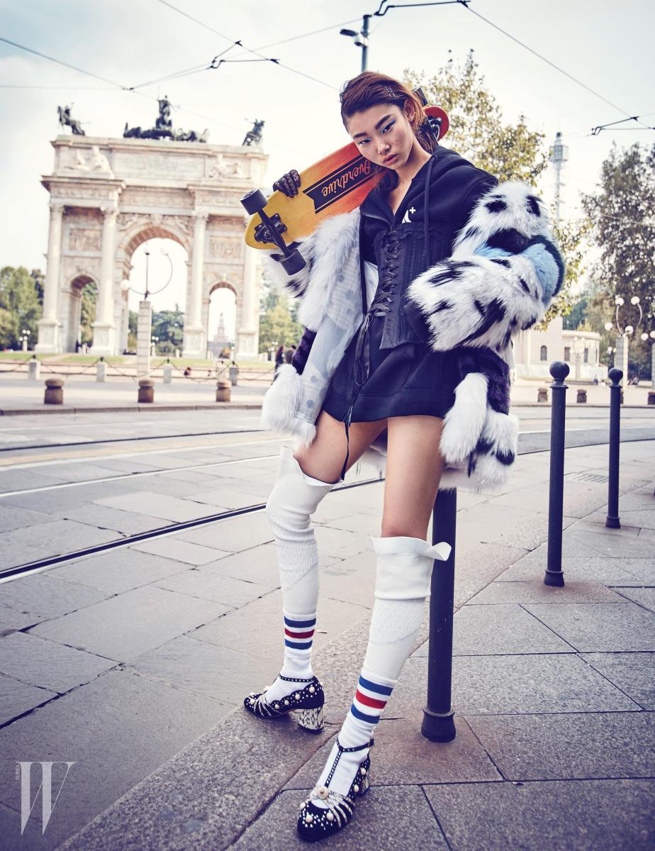 퍼 코트와 사이하이 가죽 타이츠는 Fendi, 후디 재킷은 Supercomma B, 뷔스티에는 La Perla, 진주 장식 슈즈는 Gucci 제품.