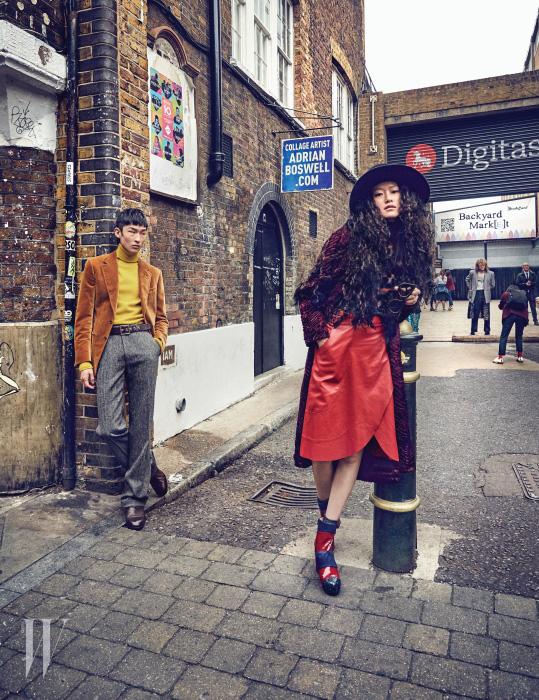 퐁리가 입은 붉은색 치마와 물방울 무늬 톱, 벨벳 코트, 플랫폼 슈즈는 모두 House of Holland, 모자는 Q millinery 제품. 김상우가 입은 터틀넥과 재킷, 울 팬츠, 가죽 벨트, 구두는 모두 Tom Ford 제품.