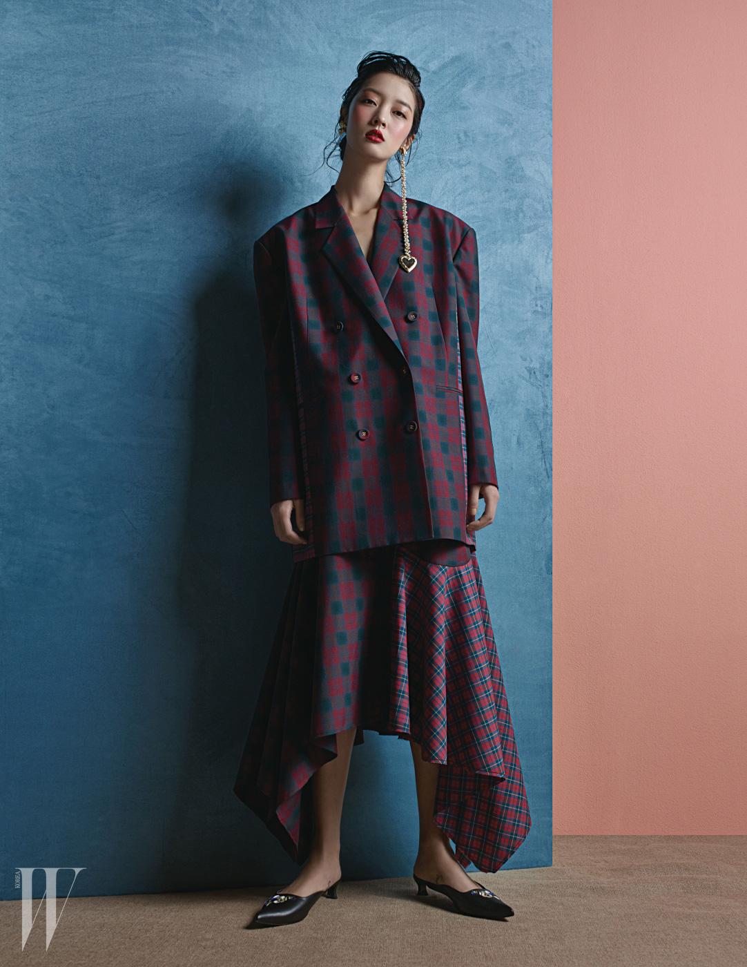 어깨가 넓은 체크무늬 재킷과 스커트, 진주 장식 비대칭 귀고리와 미드힐 슬리퍼는 모두 The Centaur 제품.