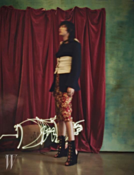 금빛 패턴이 돋보이는 붉은색 드레스, 테일러드 울 재킷, 흰색 데님 뷔스티에, 벨벳 소재 레이스업 부츠는 모두 Prada 제품.