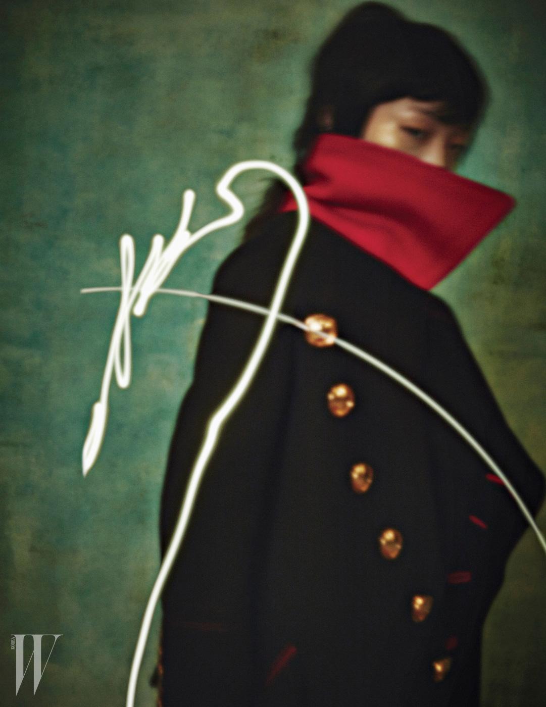금빛 단추와 붉은색 칼라 배색이 돋보이는 밀리터리 코트는 Burberry 제품.
