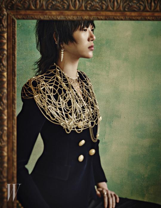 남색 벨벳 소재의 테일러드 재킷은 Balmain, 팬츠는 Haider Ackermann, 화려한 금빛 체인과 펄 장식의 주얼 케이프는 Chanel, 조형적인 진주 장식의 스트레치드 펄 귀고리와 반지는 모두 Tasaki 제품.