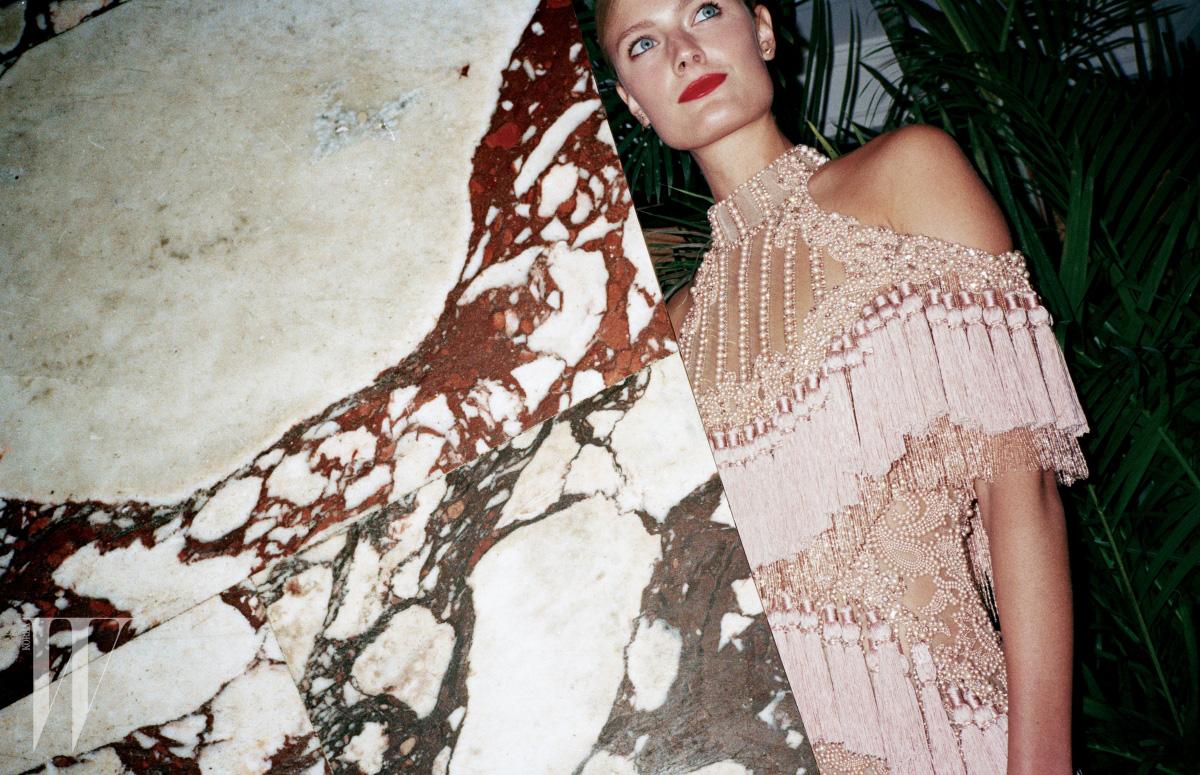 아이린이 입은 러플 블라우스와 핑크색 코르셋, 레이스와 러플로 이루어진 팬츠, 콘스탄스 자블론스키가 입은 진주, 태슬 장식 홀터넥 드레스는 모두 Balmain 제품.