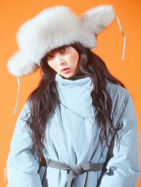 구스다운 충전재를 사용한 민트색의 롱 패딩 코트, 모피 모자, 가죽 호보백과 네오프렌 소재 부츠는 모두 Kuho 제품.