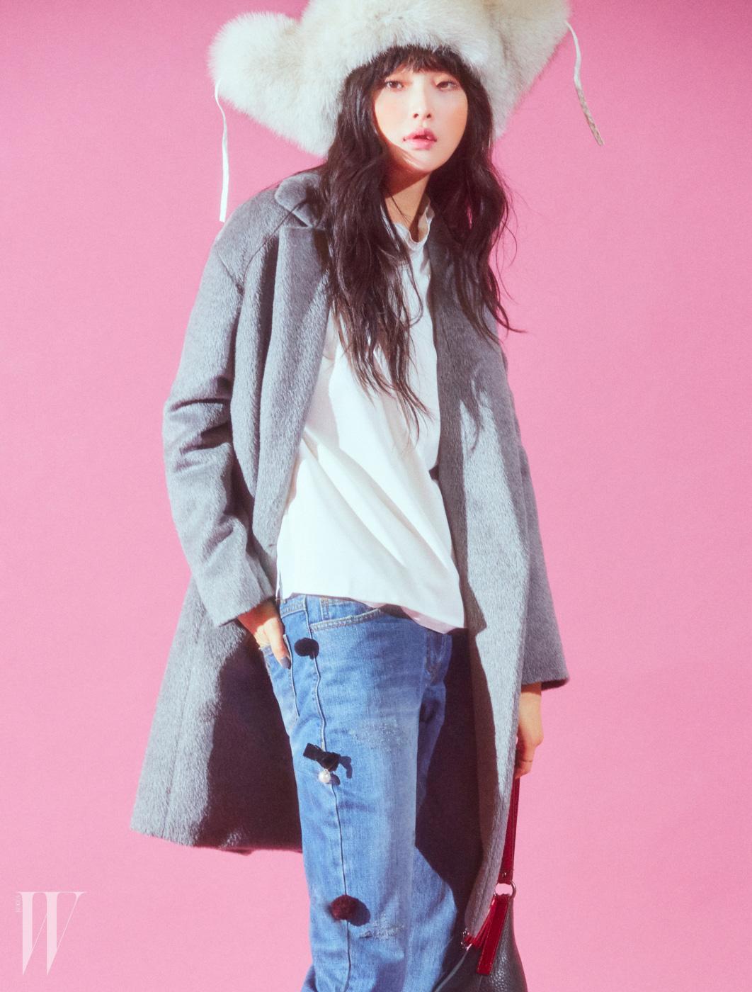 부드러운 라마혼방 모 소재의 회색 롱코트, 흰색 블라우스와 리본 장식 데님 팬츠, 트라이앵글 가죽백, 모피 모자는 모두 Kuho 제품.