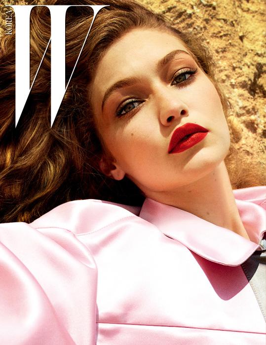 연한 분홍빛의 새틴 소재 코트는 Miu Miu 제품.