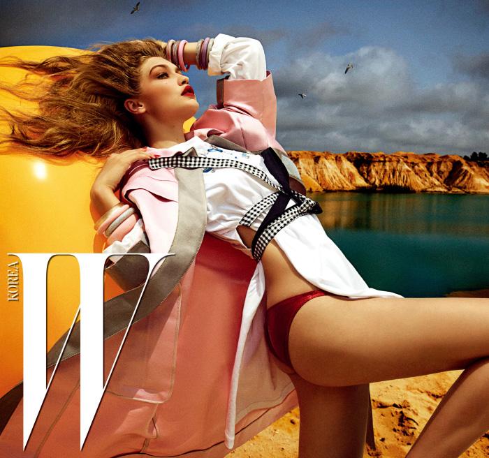 체크 리본으로 허리를 두른 크리스털 장식 티셔츠, 연한 분홍빛의 새틴 소재 코트는 Miu Miu 제품.