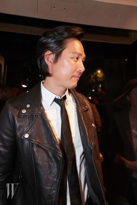배우 이정재는 골든구스디럭스 브랜드의 레터링이 멋진 가죽 재킷에 흰색 셔츠와 검정 타이로 댄디한 느낌을 보여줬다.