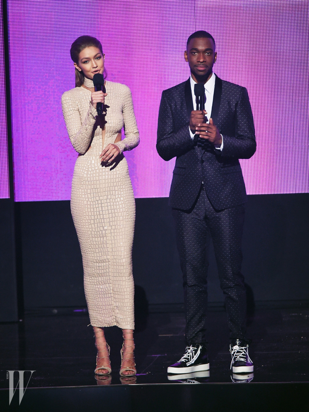 LOS ANGELES, CA - NOVEMBER 20:  Co-hosts Gigi Hadid (L) and Jay Pharoah speak onstage during the 2016 American Music Awards at Microsoft Theater on November 20, 2016 in Los Angeles, California.  (Photo by Kevin Winter/Getty Images)