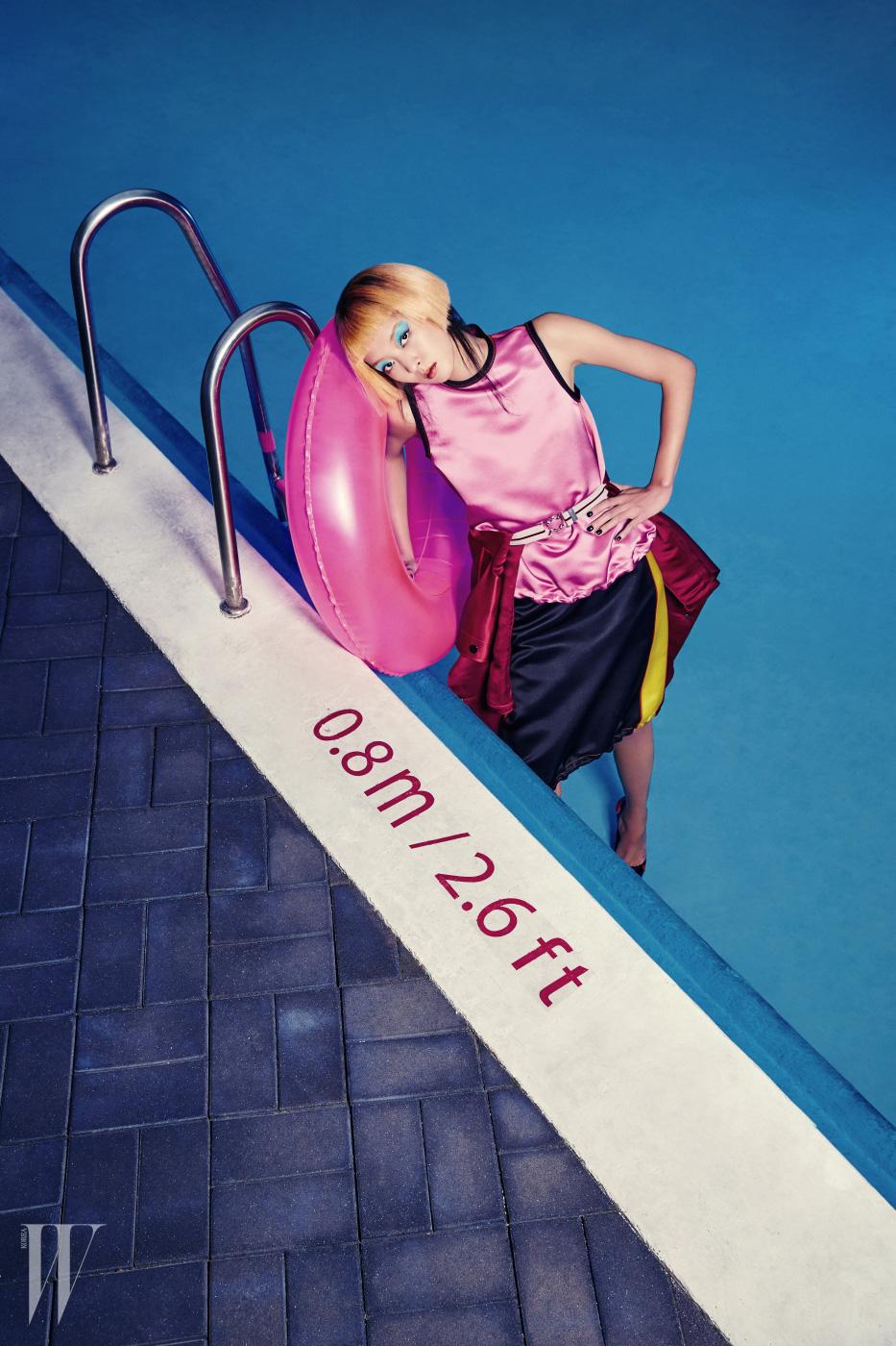 매끈한 실크 톱, 스커트, 벨트, 벨트에 넣어 연출한 코트, 슈즈는 모두 Prada 제품.