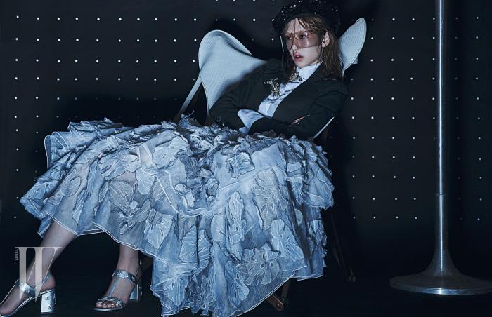흰색 셔츠와 검정 쇼트 재킷, 칼라에 장식한 브로치들, 풍성한 아플리케 장식 풀 스커트, 시퀸 장식 베레모와 실버 가죽 샌들은 모두 Chanel 제품. 조형적인 디자인이 돋보이는 순백의 가죽 의자는 Henri Beguelin 제품.
