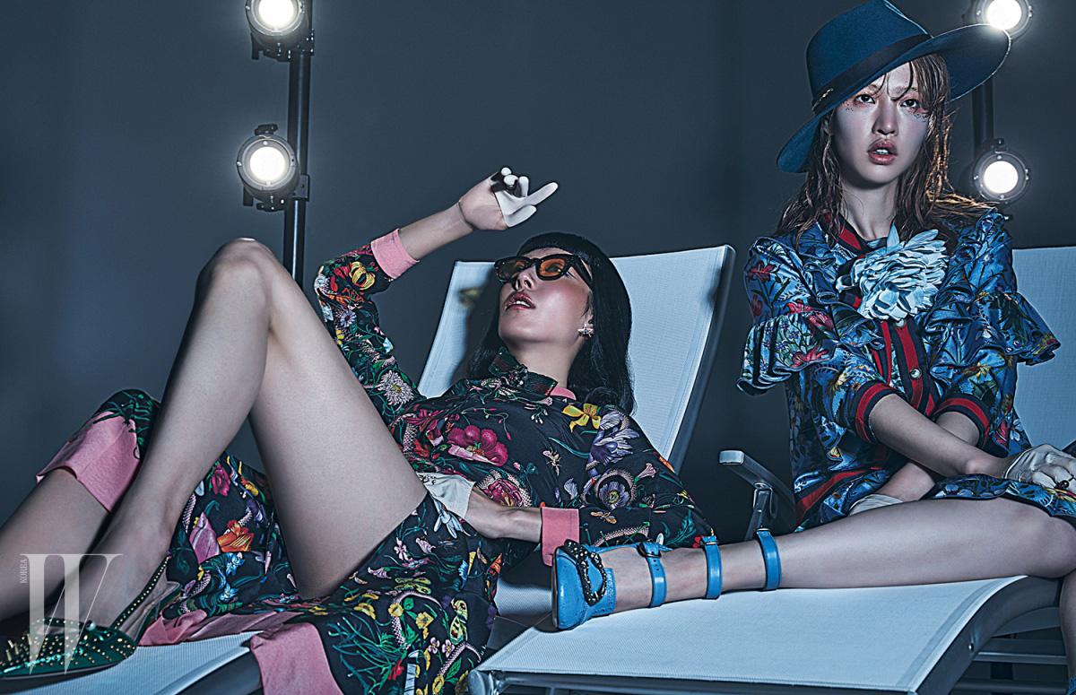 지현정이 착용한 꽃무늬 드레스와 펌프스는 Gucci, 별 모티프의 진주 장식 귀고리와 반지는 Tasaki, 선글라스는 Gentle Monster 제품. 유지안이 착용한 코르사주 브로치 장식의 꽃무늬 러플 드레스와 스트랩 슈즈는 Gucci, 우아한 실루엣의 모자는 Hermes, 진주 장식 반지는 Tasaki 제품.
