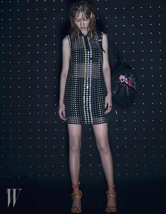 스톤 장식의 셔츠 드레스와 슈즈는 Versace, 백팩은 Saint Laurent, 검정 진주 반지는 Tasaki 제품.