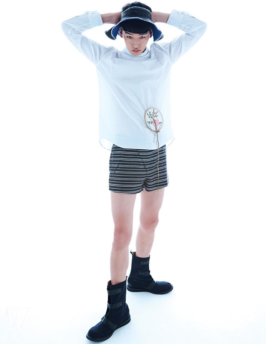 자수가 패치워크된 흰색 하이네크 셔츠, 가로 스트라이프 패턴의 쇼츠, 챙이 넓은 바이저 햇과 벨트 장식 부츠는 모두 M NN 제품.