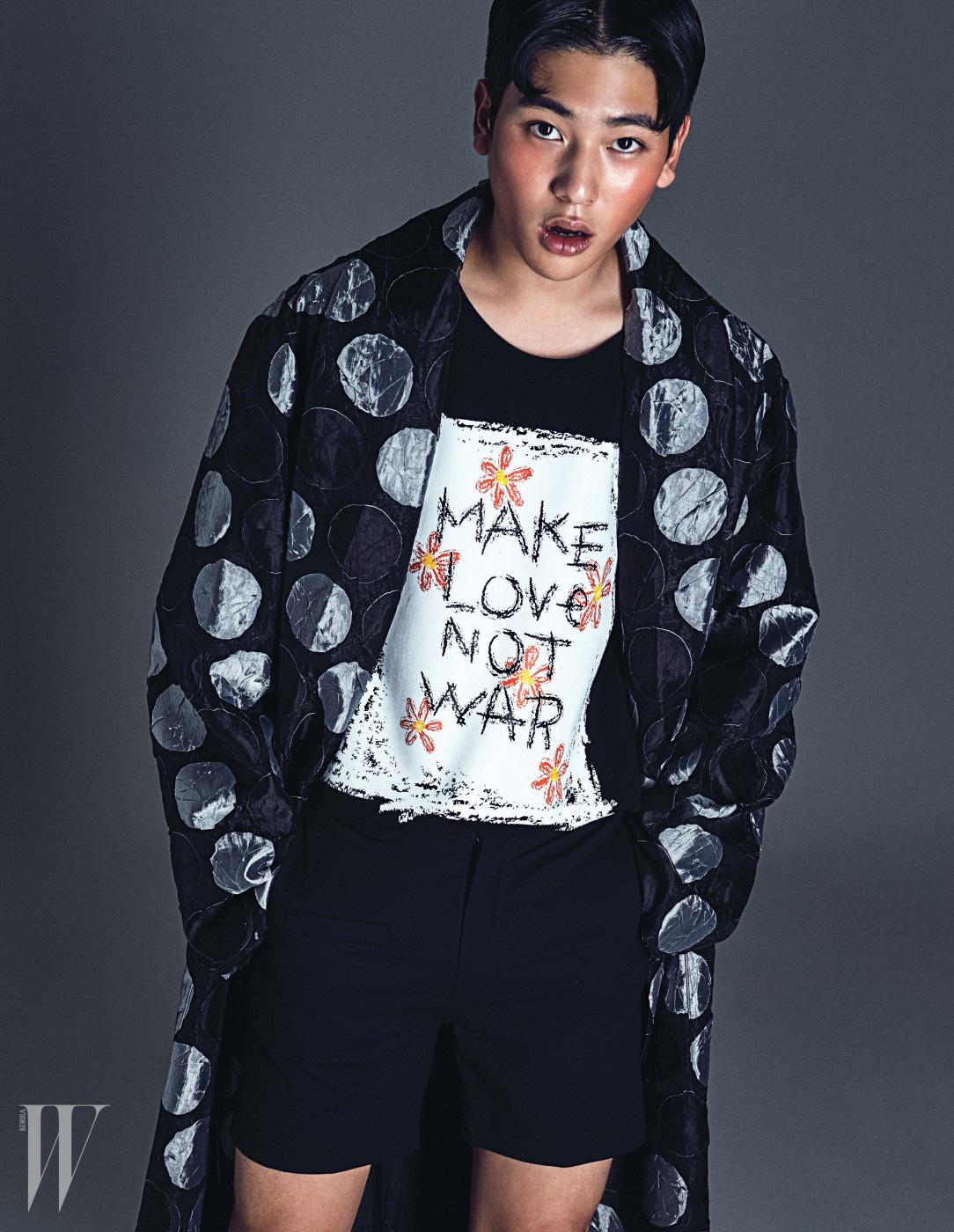 달이 프린트된 얇은 로브형 코트, 영문 프린트의 검은색 티셔츠와 검은색 쇼츠는 모두 Munsoo Kwon 제품.