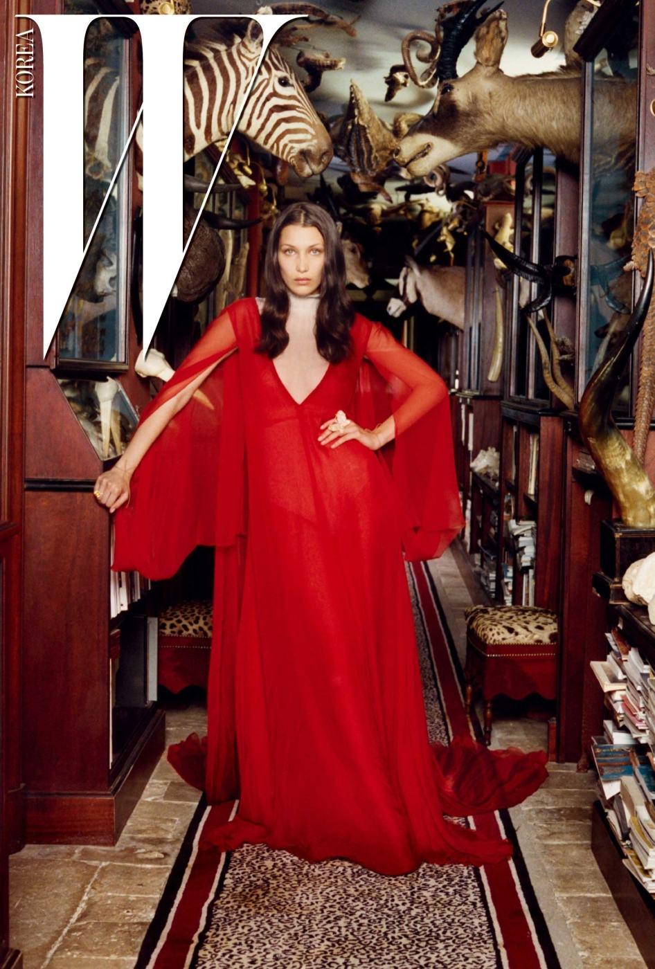 붉은색 케이프 드레스와 보디슈트는 Valentino Haute Couture. 커다란 반지는 Chopard 제품.