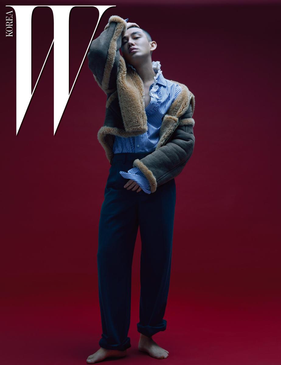 칼라가 넓은 무톤 재킷, 프릴 장식 줄무늬 셔츠, 통 넓은 팬츠는 모두 Burberry 제품.