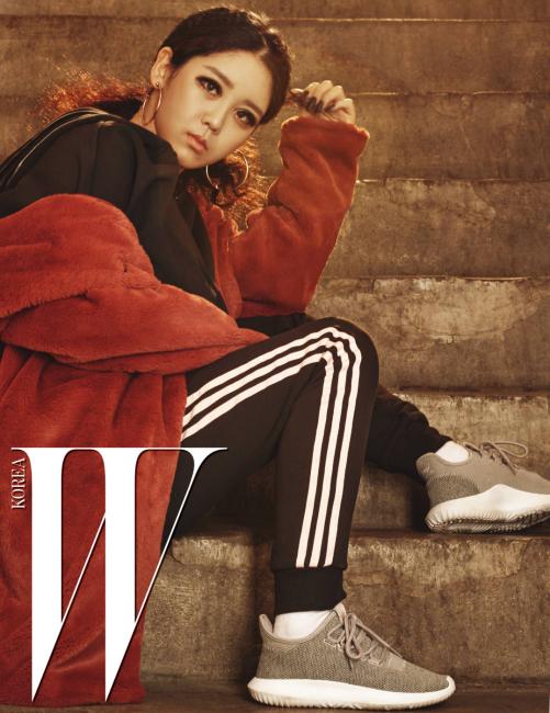 래퍼 트루디가 착용한 회색 운동화는 Tubular Shadow, 시스루 소재가 믹스된 후드 집업과 스웨트 팬츠는 Adidas Originals, 핑크색 페이크 퍼 코트는 Mischef 제품.
