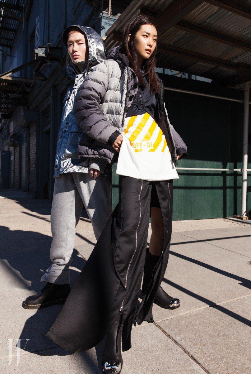 몽클레르 O 컬렉션 점퍼를 입고 뉴욕 미트패킹 스트리트에서 포즈를 취한 노마한과 곽지영. 아웃도어에서도, 도심에서도 어울리며 가지고 있는 어떤 옷과도 믹스매치할 수 있는 것이 장점이다. 노마한이 입은 팬츠는 몽클레르, 곽지영이 입은 점퍼는 오프화이트x몽클레르, 티셔츠와 지퍼 장식의 팬츠, 메탈 캡 토 부티는 오프화이트 제품.