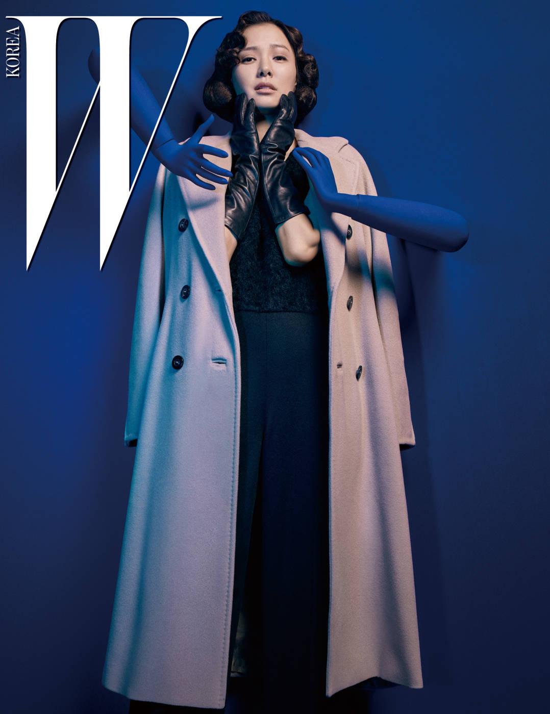 막스마라의 아이코닉한 까샤 컬러 101801 코트와 안에 입은 검은색 점프슈트, 펌프스, 가죽 장갑은 모두 Max Mara 제품.