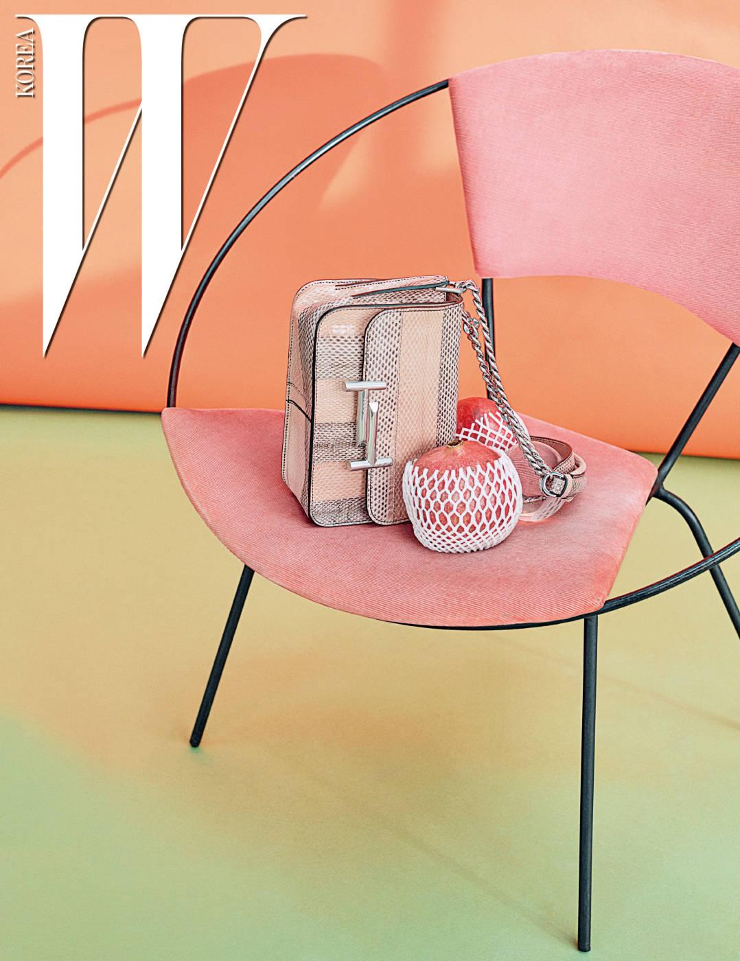 감미로운 파스텔톤이 돋보이는 더블 T 로고 장식의 이그조틱 가죽 소재 체인 숄더백은 Tod's 제품.