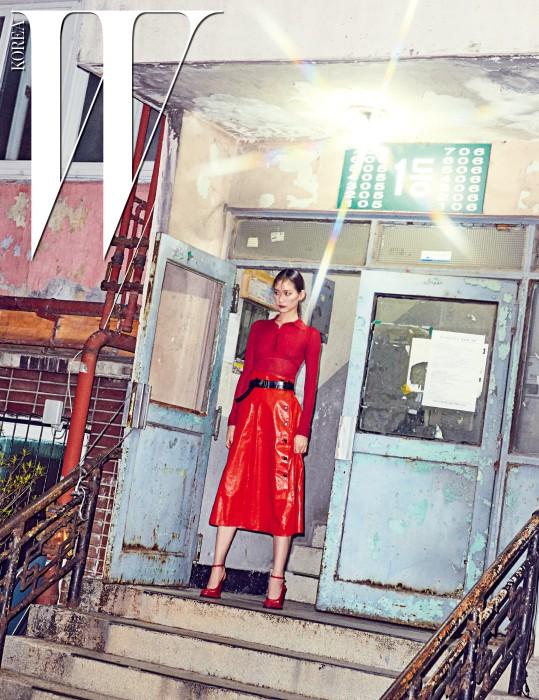 복고적 무드의 니트 톱과 벨트가 장식된 램스킨 스커트, 페이턴트 소재의 빨간색 스트랩 슈즈는 모두 Bottega Veneta 제품.