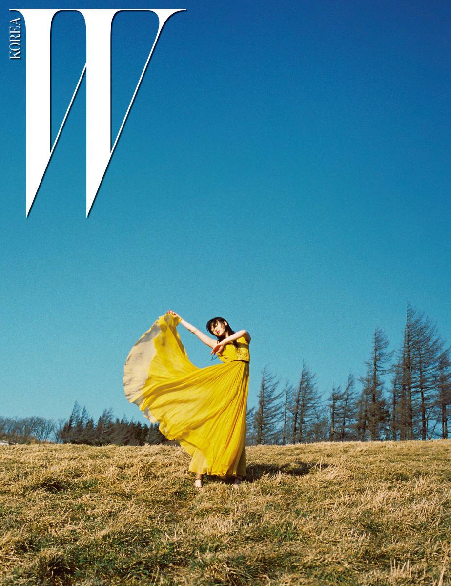 가느다란 주름 장식이 풍성한 샛노란 롱 드레스는 Giambattista Valli의 리조트 컬렉션 제품.