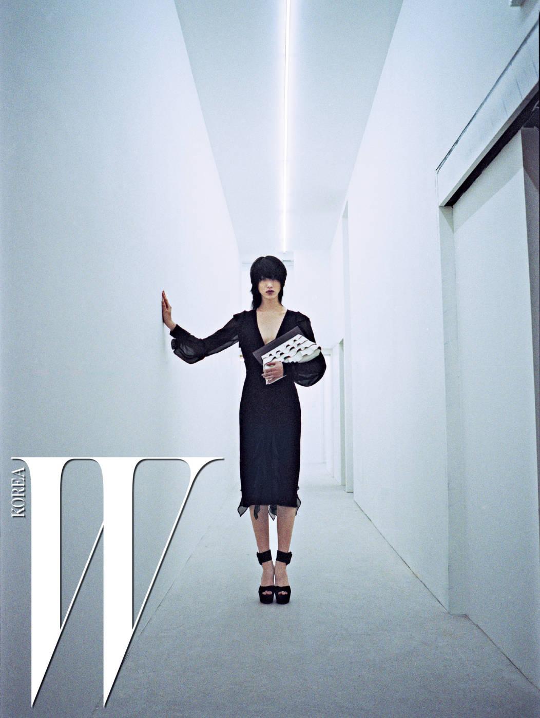 러플 장식의 관능적인 블랙 드레스와 구조적인 형태의 클러치, 대담한 스트랩 샌들은 모두 Michael Kors Collection 제품.
