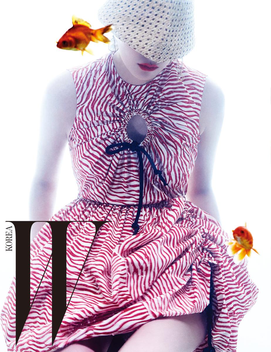 매듭과 컷아웃 장식이 어우러진 물결무늬 벌룬 드레스와 베이지색 라피아 모자, 바로크 진주와 물고기 모양 귀고리는 모두 Sportmax 제품.