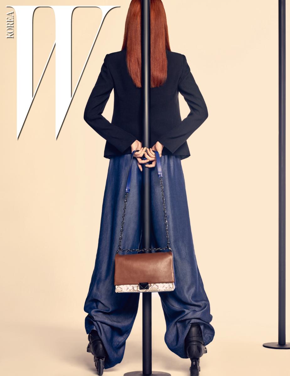 단정한 느낌의 검은색 테일러드 재킷, 얇은 데님 소재의 통이 넓은 팬츠, 갈색과 파랑, 뱀피 가죽의 조합이 멋진 사각 체인 백은 모두 Emporio Armani 제품