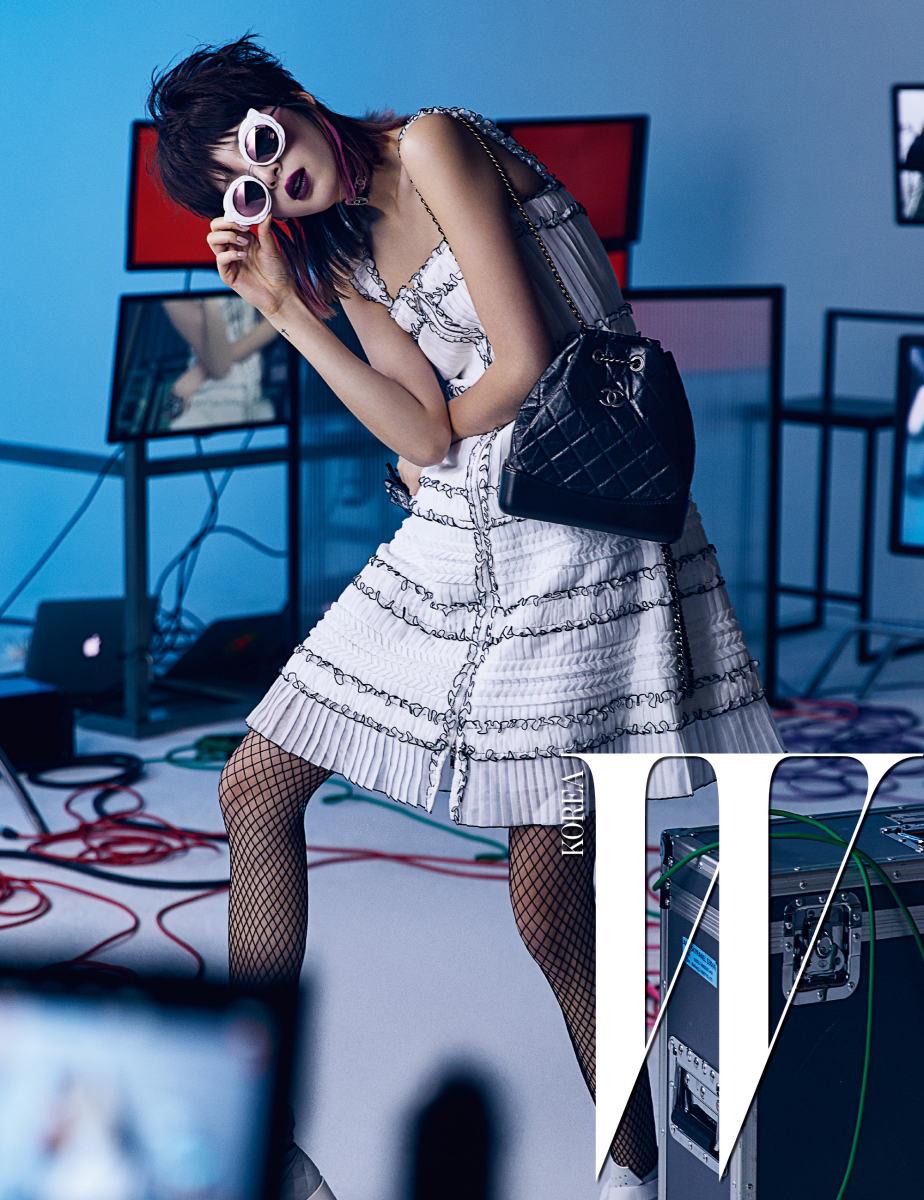 프릴 장식의 화이트 집업 드레스, 카멜리아 모티프의 펑키한 선글라스, 더블 스트랩으로 다양한 연출이 가능한 가브리엘 백, 슈즈는 모두 Chanel 제품.