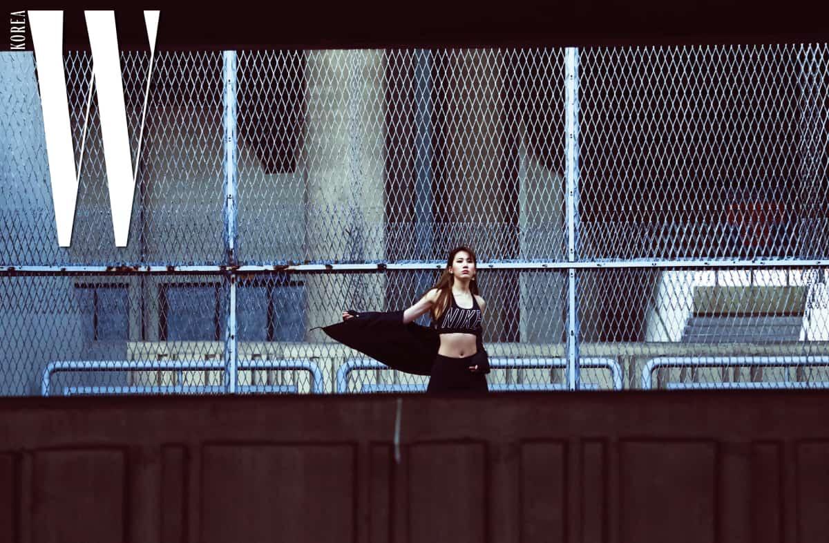 후디가 입은 타이포 로고 장식의 브라와 타이츠는 Nike, 커팅이 독특한 귀고리는 Numbering Seoul, 가볍게 걸치기 좋은 점퍼는 Thrasher by ETC Seoul 제품.