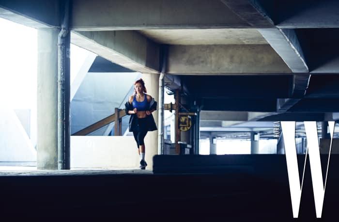 이상화가 입은 색감이 선명한 브라와 활동성 좋은 타이츠, 트레이닝화는 모두 Nike, 어깨가 드러나도록 연출한 점퍼는 Obey by ETC Seoul, 두 개를 레이어드한 실버 목걸이는 Numbering Seoul 제품.
