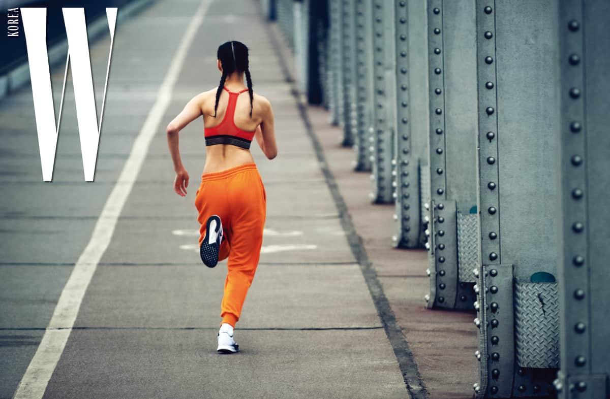 김설희가 입은 강렬한 색감의 브라와 러닝에 최적화된 러닝화, 양말은 모두 Nike, 경쾌한 오렌지 조거 팬츠는 Used Future 제품.