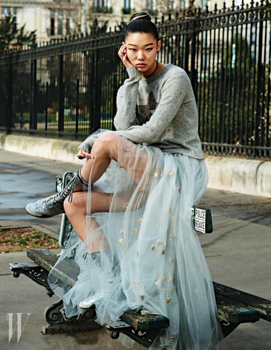 회색 니트와 벌무늬를 섬세하게 수놓은 샤 스커트, 레이스업 부츠와 초커, 반지는 모두 Dior 제품.