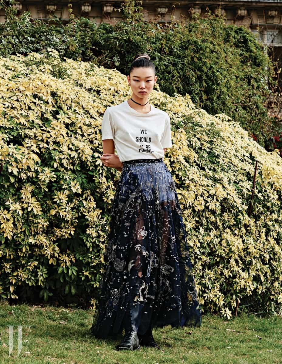 타이포 티셔츠와 비즈 장식 샤 스커트, 흰색 브리프, 레이스업 부츠, 초커와 귀고리는 모두 Dior 제품.