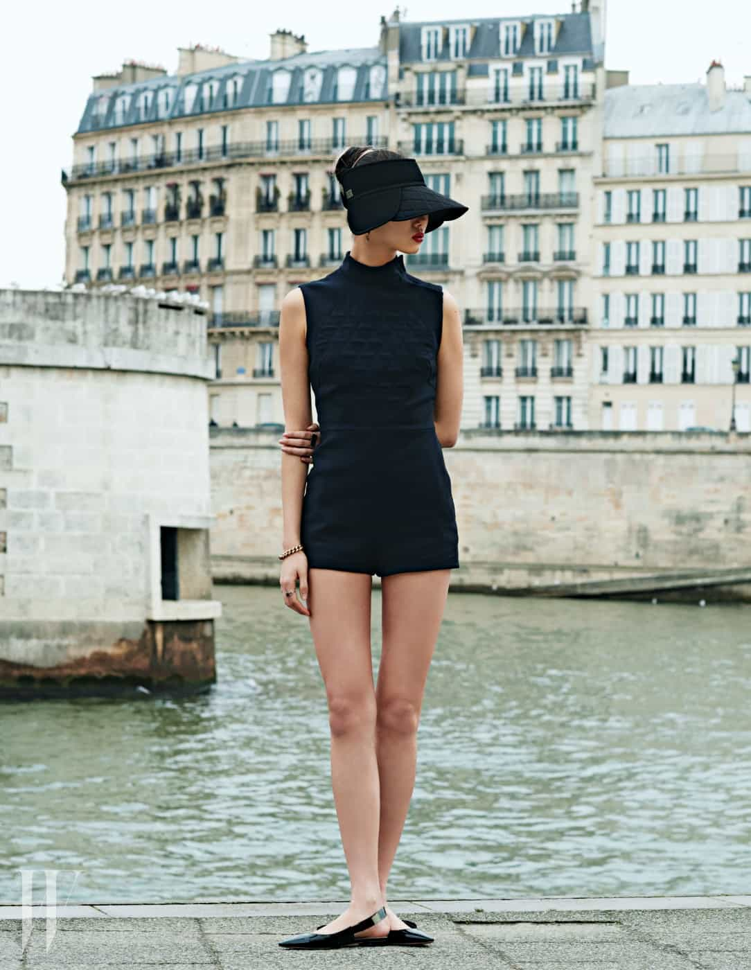 검정 선캡과 슬리브리스 점프슈트, 체인 팔찌와 반지, 앞코가 뾰족한 플랫 슈즈는 모두 Dior 제품.