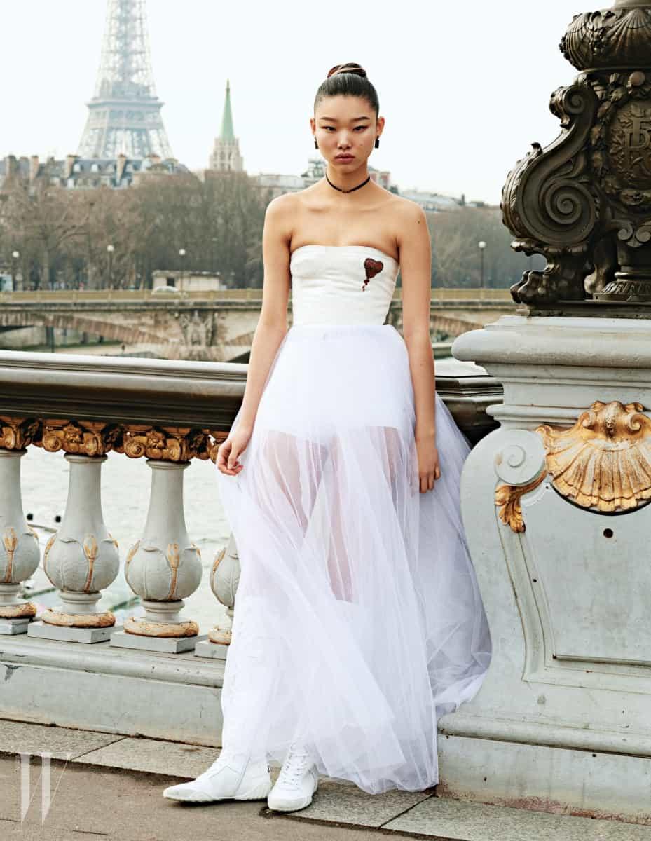 가슴의 붉은색 하트 무늬 장식이 위트 있는 튜브톱 샤 드레스와 속에 입은 흰색 브리프, 레이스업 부츠, 초커, 귀고리는 모두 Dior 제품.
