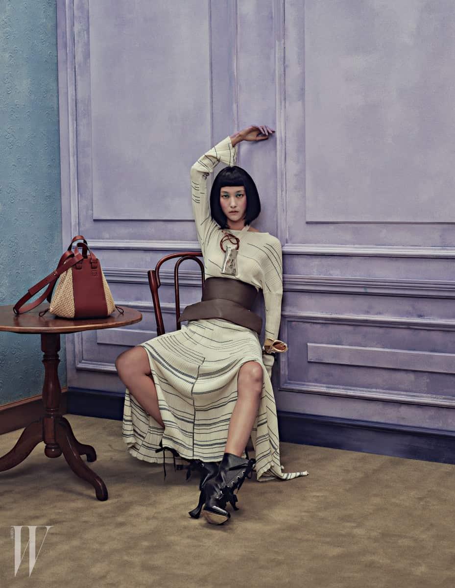 푸른색 줄무늬를 더한 니트 드레스, 대담한 형태의 펜던트가 돋보이는 이케바나 베이스 목걸이, 소재의 믹스 매치가 특징인 해먹 라피아 백(Hammock Raffia Bag), 검정 레이스업 앵클부츠는 모두 Loewe 제품.