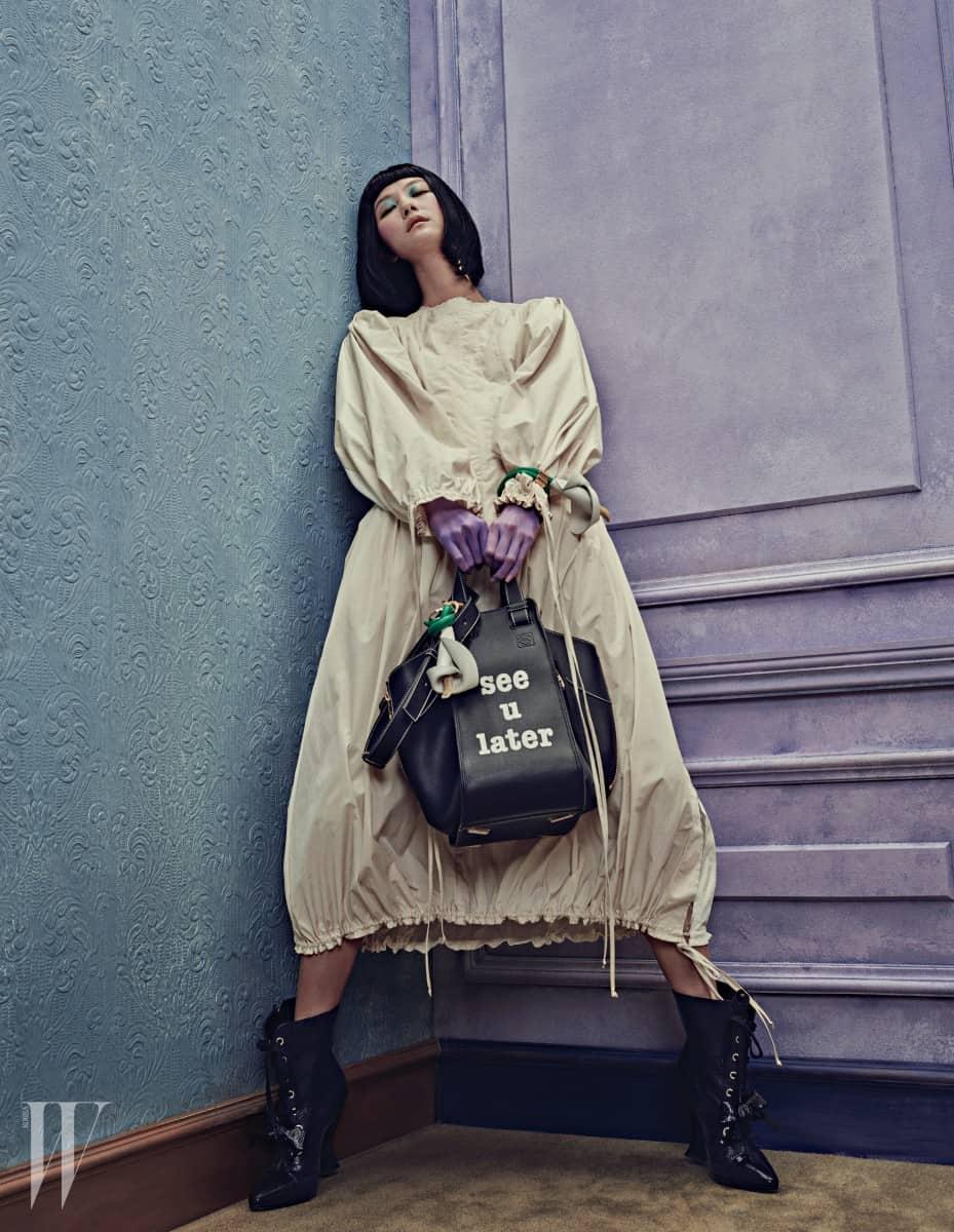 칼리코 벌룬 드레스, 골드 빈티지 마스크 귀고리, 코르사주 가죽 참을 장식한 위트 있는 문구의 해먹 씨 유 레이터 백(Hammock See U Later Bag), 카라꽃에서 영감을 받은 입체적인 코르사주 장식의 가죽 팔찌, 검정 레이스업 앵클부츠는 모두 Loewe 제품.
