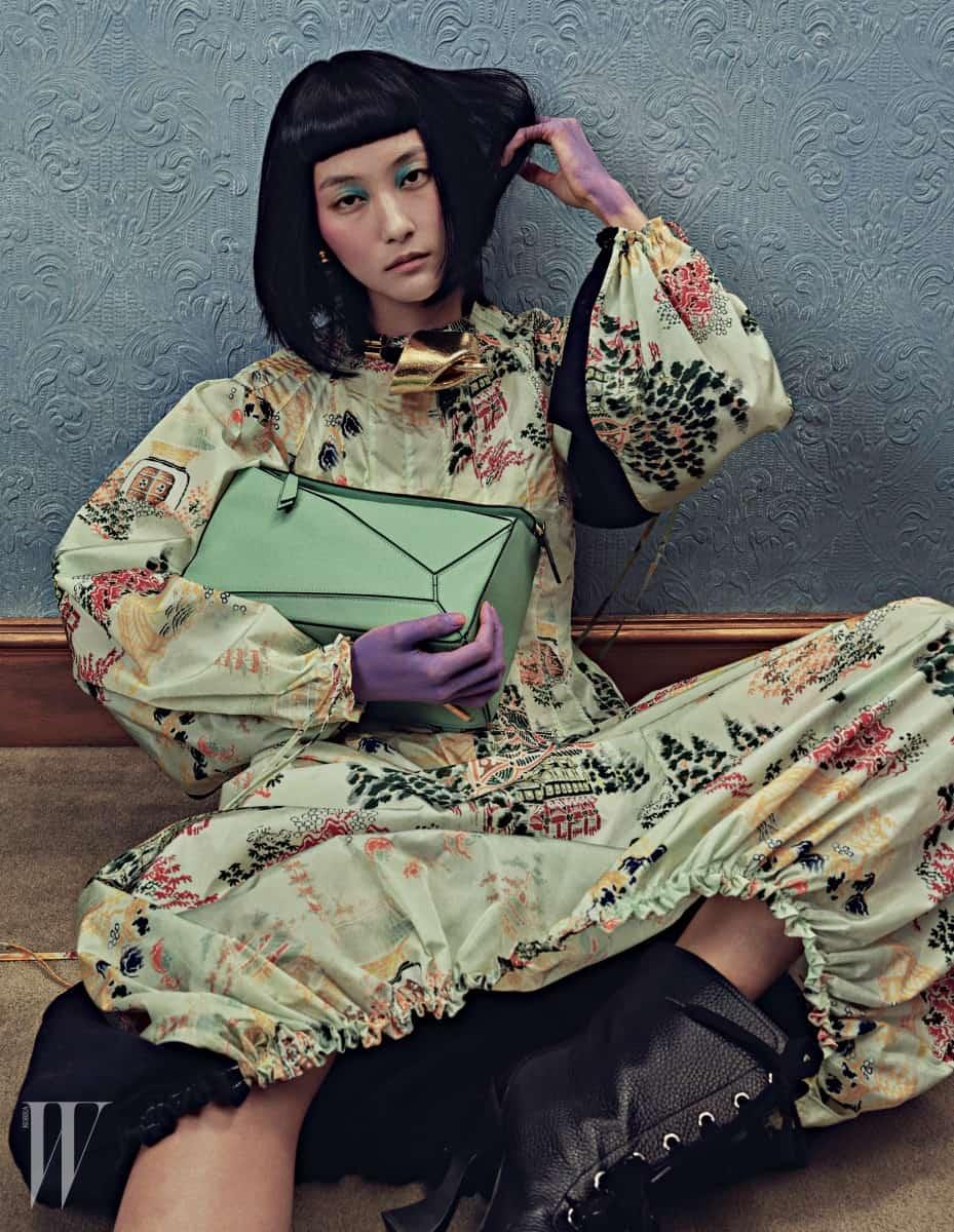 섬세한 자수 장식이 고풍스러운 드레스, 귀고리, 목걸이로 연출한 금빛 코르사주 장식의 가죽 팔찌, 씨-워터 그린 색상의 기하학적인 퍼즐 백(Puzzle Bag), 검정 레이스업 앵클부츠는 모두 Loewe 제품.