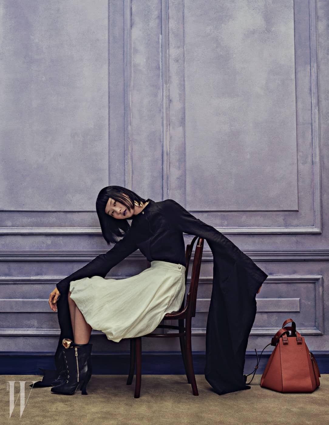 긴소매가 아티스틱한 분위기를 자아내는 검정 집업 쇼트 재킷, 벌룬 스커트, 골드 빈티지 마스크 귀고리, 조형적인 형태와 자연스러운 색감이 돋보이는 해먹 백 탠(Hammock Bag Tan), 발목에 연출한 금빛 코르사주 장식 가죽 팔찌, 검정 레이스업 앵클부츠는 모두 Loewe 제품.