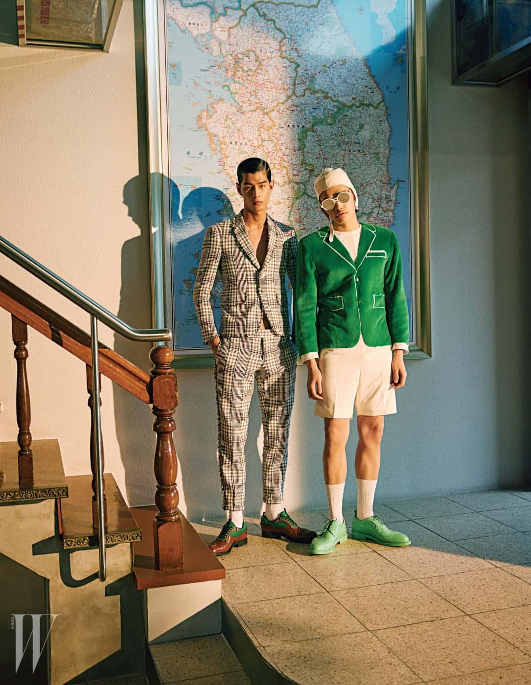 왼쪽부터ㅣ태은이 입은 체크무늬 슈트는 Thom Browne, 슈즈는 Prada 제품. 정혁이 입은 점프슈트, 양말, 모자, 슈즈, 선글라스는 모두 Thom Browne 제품.