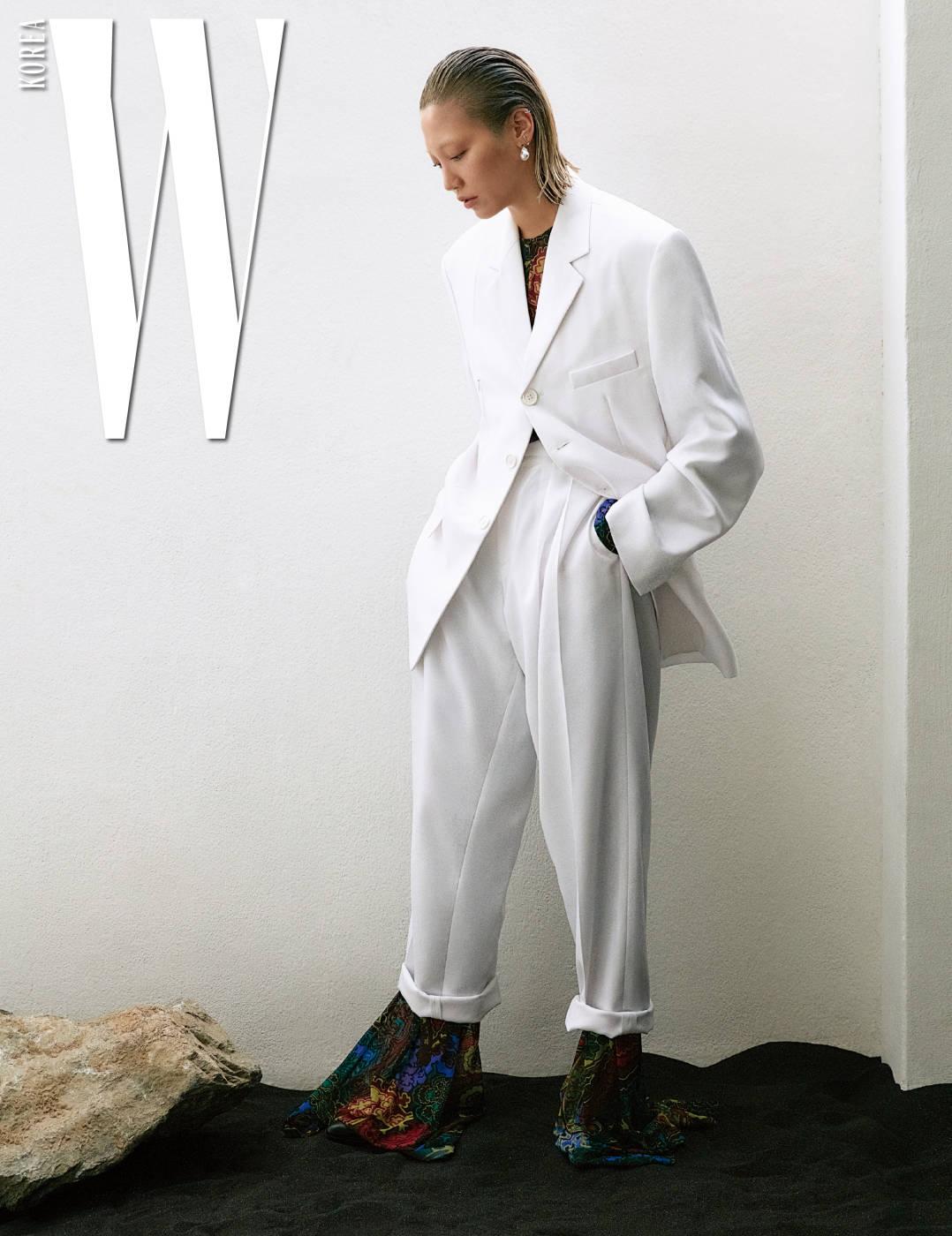 순백의 테일러드 재킷과 롤업 팬츠, 안에 매치한 화려한 프린트의 시스루 점프슈트, 진주 귀고리, 슈즈는 모두 Celine 제품.