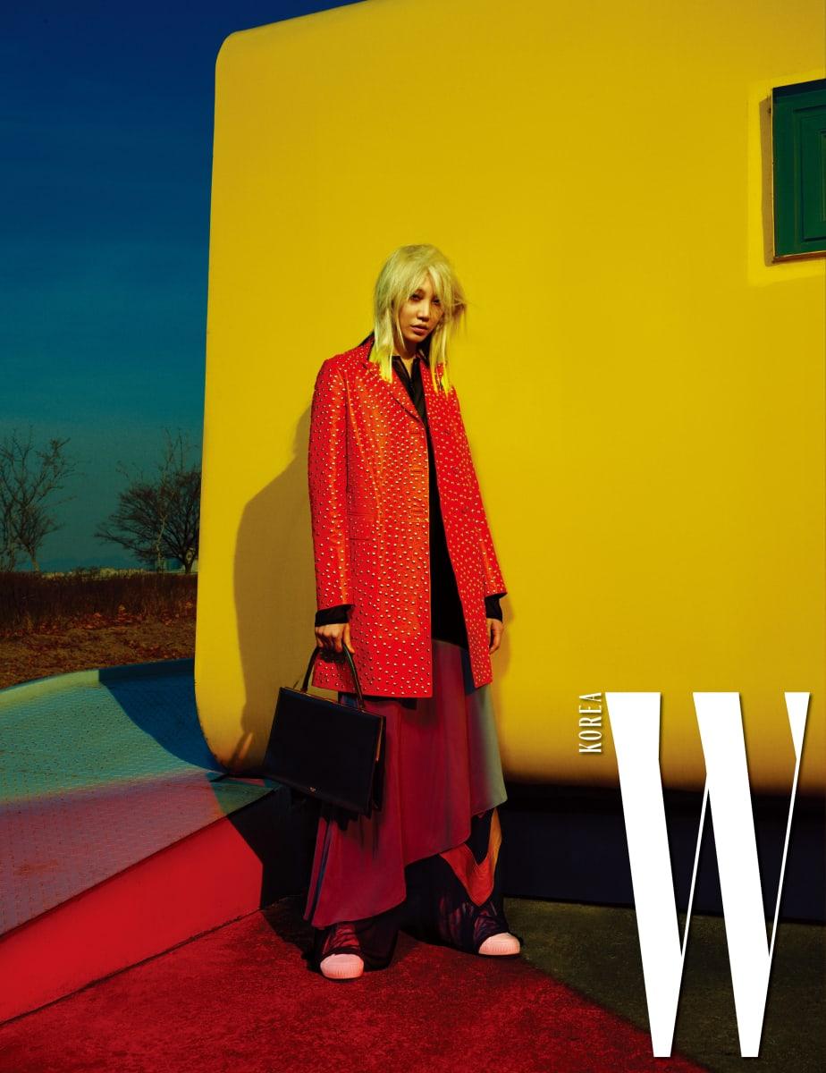 스터드 장식의 주홍색 롱 재킷과 검정 블라우스, 회색 바이어스 컷의 스커트, 검정 와이드 팬츠, 미니멀한 형태의 사각 토트백, 슈즈는 모두 Celine 제품.