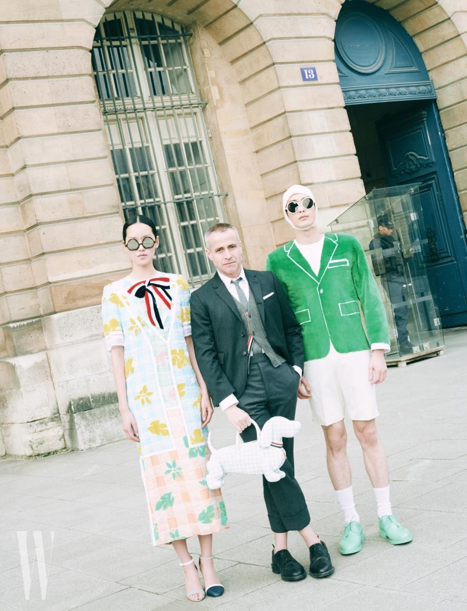 퐁리가 입은 리본 장식 체크 꽃무늬 드레스, 언밸런스 앵클 스트랩 샌들, 미러 선글라스, 톰 브라운이 들고 있는 체크무늬 핵터 백, 서하가 입은 초록색 페이크 퍼 점프슈트, 수영 모자와 양말, 민트색 러버 소재 슈즈는 모두 Thom Browne 제품.